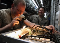 Senior Airman Ross Lemp and Tech. Sgt. Michael Sequin, 763rd Expeditionary Reconnaissance Squadron electronic warfare maintainers, examine the information systems onboard a RC-135V/W Rivet Joint May 6, 2013, at the 379th Air Expeditionary Wing, Southwest Asia. The RC-135's are primarily used as an intelligence, surveillance and reconnaissance platform; picking up real-time information on oppositional forces. Lemp and Sequin are deployed from Offutt Air Force Base, Neb. (U.S. Air Force photo/Staff Sgt. Joel Mease)