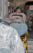 Capt. Natasha Sommerville, 379th Expeditionary Medical Operations Squadron nurse, practices responding to mock patient, Senior Airman Jason Henderson, 379th EMDOS medical technician, in an ambulance, May 9, 2013, at the 379th Air Expeditionary Wing's medical facility. Sommerville and Henderson deployed here from Joint Base Langley-Eustis, Va. The Air Force Medical Service is celebrating Nurse and Medical Technician week May 6 - 12. (U.S. Air Force photo/Senior Airman Benjamin Stratton)