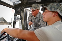 Staff Sgt. Roque Solis explains the finer operations of his favorite piece of equipment, the 50K Rough Terrain Container Handler, to Senior Airman Carlos Cassano at the 379th Air Expeditionary Wing in Southwest Asia, May 14, 2013. Solis and Cassano are 379th Expeditionary Logistics Readiness Squadron vehicle operators. Solis deployed from Fairchild Air Force Base, Wash., and Cassano from Luke AFB, Ariz. (U.S. Air Force photo/Senior Airman Benjamin Stratton)