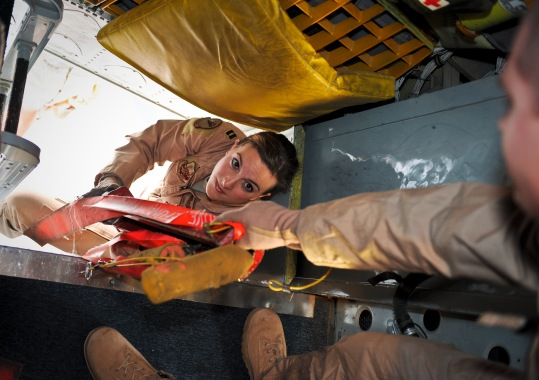 """Capt. Emma House hands Senior Airman Rich Bradford safety lines during pre-flight checks on aircraft """"57-1419,"""" May 18, 2013, at the 379th Air Expeditionary Wing in Southwest Asia. House is a 340th Expeditionary Air Refueling Squadron aircraft commander and Bradford is a 340th EARS boom operator. Both are deployed from Scott Air Force Base, Ill. Aircraft 57-1419 is a KC-135 Stratotanker deployed from the 190th Air Refueling Wing of the Kansas Air National Guard. (U.S. Air Force photo/Senior Airman Benjamin Stratton)"""