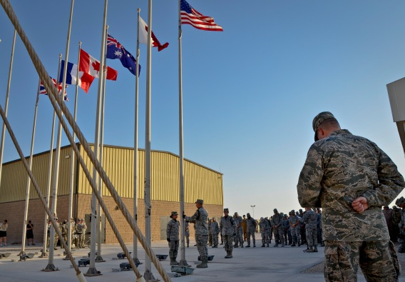Honor guard members deployed to the 379th Air Expeditionary Wing attend to the colors as Chaplain (Col.) Bruce Glover gives the invocation during a Memorial Day retreat ceremony, May 27, 2013, at Memorial Plaza in Southwest Asia. Glover is the 379th AEW wing chaplain. (U.S. Air Force photo/Senior Airman Benjamin Stratton)