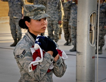 Airman 1st Class Lena Lau secures the American flag during a Memorial Day retreat ceremony, May 27, 2013, at Memorial Plaza in Southwest Asia. Lau is a member of the 379th Air Expeditionary Wing honor guard. Military retreat ceremonies serve a twofold purpose: to signal the end of the official duty day and to pay respect to the U.S. flag. (U.S. Air Force photo/Senior Airman Benjamin Stratton)