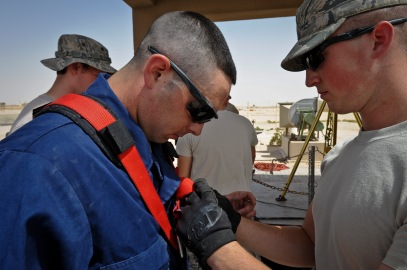 Senior Airman Joshua Paul straps a harness onto Airman 1st Class Devin Walsh as the team prepares to fix a broken sewage lift station pump at the 379th Air Expeditionary Wing in Southwest Asia, June 18, 2013. Paul is a 379th Expeditionary Civil Engineer Squadron firefighter deployed from Andrews Air Force Base, Md., and Walsh is a 379th ECES water and fuel systems maintenance technician deployed from Elmendorf AFB, Alaska. (U.S. Air Force photo/Senior Airman Benjamin Stratton)