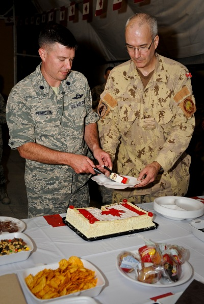 U.S. Air Force Lt. Col. Darin Humiston gives Canadian Air Forces Maj. Mike Hagen a piece of cake during the Canada Day celebration at the 379th Air Expeditionary Wing in Southwest Asia, July 1, 2013. Humiston is the U.S. Air Force 71st Expeditionary Air Control Squadron commander and Hagen is the Canadian 71st EACS commander. Deployed service members shared in activities ranging from a Canadian trivia game, guitar solo and board games. (U.S. Air Force photo/Senior Airman Benjamin Stratton)
