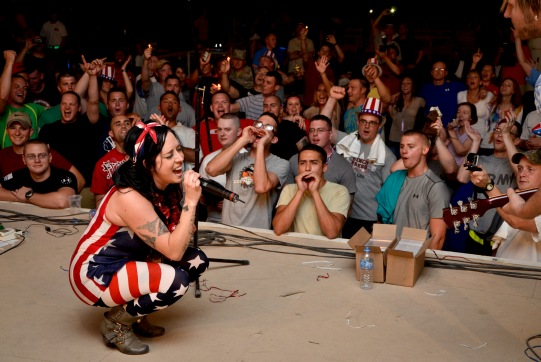 The Ringers lead singer, Kat Perkins, serenades 379th Air Expeditionary Wing service members during the July Fourth celebration at the 379th AEW in Southwest Asia, July 4, 2013. The Ringers are a wedding and event band on tour from Minneapolis, Minn., and are back by popular request. Along with playing in this group, Kat fronts the award-winning, internationally-recognized Twin Cities based, Scarlet Haze and has been in the industry since she was 15 years old. Grand Slam service members enjoyed music in genres ranging from Rock and Pop to Country and Rhythm and Blues with titles tailored for celebrating America's freedom. (U.S. Air Force photo/Senior Airman Benjamin Stratton)