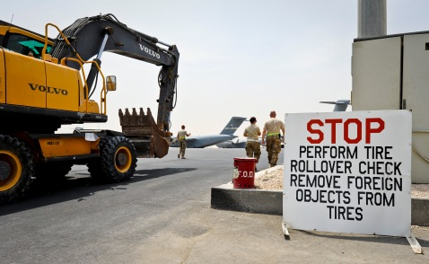 After performing a foreign object check on its tires, an excavator is moved to a C-17 Globemaster III at the 379th Air Expeditionary Wing in Southwest Asia, July 17, 2013. The C-17 will fly the heavy equipment to a forward operating location in Afghanistan where 1st Expeditionary Civil Engineer Group units will use it to support ongoing Operation Enduring Freedom missions. (U.S. Air Force photo/Senior Airman Benjamin Stratton)