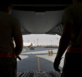Airmen from the 8th Expeditionary Air Mobility Squadron prepare as an excavator is brought on board a C-17 Globemaster III at the 379th Air Expeditionary Wing in Southwest Asia, July 17, 2013. The C-17 will fly the heavy equipment to a forward operating location in Afghanistan where 1st Expeditionary Civil Engineer Group units will use it to support ongoing Operation Enduring Freedom missions. (U.S. Air Force photo/Senior Airman Benjamin Stratton)