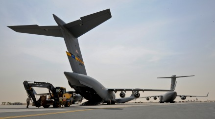 Airmen from the 8th Expeditionary Air Mobility Squadron and 557th Expeditionary RED HORSE Squadron load an excavator onto a C-17 Globemaster III at the 379th Air Expeditionary Wing in Southwest Asia, July 17, 2013. The C-17 will fly the heavy equipment to a forward operating location in Afghanistan where 1st Expeditionary Civil Engineer Group units will use it to support ongoing Operation Enduring Freedom missions. (U.S. Air Force photo/Senior Airman Benjamin Stratton)