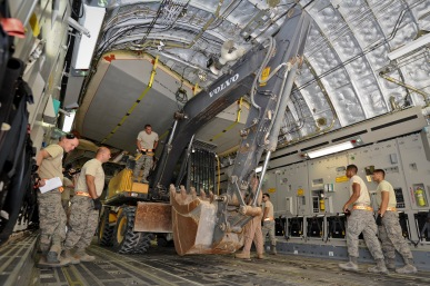Airmen from the 8th Expeditionary Air Mobility Squadron, 557th Expeditionary RED HORSE Squadron and loadmasters from the 816th Expeditionary Airlift Squadron load an excavator onto a C-17 Globemaster III at the 379th Air Expeditionary Wing in Southwest Asia, July 17, 2013. The C-17 will fly the heavy equipment to a forward operating location in Afghanistan where 1st Expeditionary Civil Engineer Group units will use it to support ongoing Operation Enduring Freedom missions. (U.S. Air Force photo/Senior Airman Benjamin Stratton)