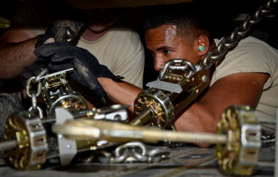 Senior Airman Marcanthony Khan secures an excavator with chains onboard a C-17 Globemaster III at the 379th Air Expeditionary Wing in Southwest Asia, July 17, 2013. Khan is an 8th Expeditionary Air Mobility Squadron air transportation technician deployed from Joint Base Charleston, S.C. (U.S. Air Force photo/Senior Airman Benjamin Stratton)