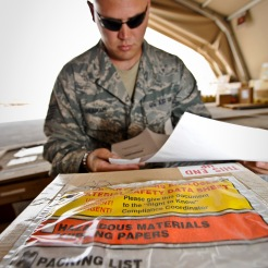 Tech. Sgt. Nicholas Graham inspects the paperwork for a hazardous materials labeled box at the 379th Air Expeditionary Wing in Southwest Asia, July 22, 2013. Graham is the 8th Expeditionary Air Mobility Squadron cargo processing and special handling NCO in charge currently on a remote tour here. (U.S. Air Force photo/Senior Airman Benjamin Stratton)