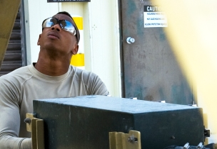 Senior Airman Maurice Kelly performs routine maintenance on a Tunner 60K aircraft cargo loader at the 379th Air Expeditionary Wing in Southwest Asia, July 31, 2013. Kelly is a 379th Expeditionary Logistics Readiness Squadron material handling and equipment mechanic deployed from Seymour Johnson Air Force Base, N.C. (U.S. Air Force photo/Senior Airman Benjamin Stratton)