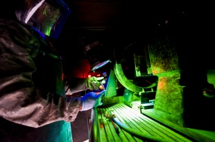 Senior Airman Darnell McConnell inspects an aircraft part for cracks by means of a magnetic particle inspection at the 379th Air Expeditionary Wing in Southwest Asia, Aug. 6, 2013. MPI is a nondestructive inspection process for detecting surface and slightly subsurface discontinuities in materials such as iron, nickel and cobalt. McConnell is a 379th Expeditionary Maintenance Squadron NDI journeyman deployed and hails from Colorado Springs, Colo. (U.S. Air Force photo/Senior Airman Benjamin Stratton)