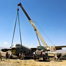 Airmen forward deployed from the 379th Air Expeditionary Wing assist in a crash damage reclamation and demilitarization project of a C-130J Super Hercules at a forward operating base in Afghanistan, July 3, 2013. The team recovered 250 components totaling more than $20 million. (U.S. Air Force photo)