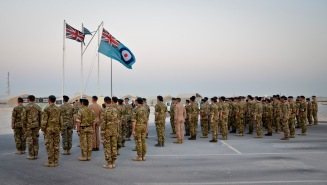 "Royal Air Force service members respectfully stand at attention as Capt. Haley Armstrong plays ""Last Post"" and ""Reveille"" on her trumpet during the Battle of Britain Day parade ceremony at the 379th Air Expeditionary Wing in Southwest Asia, Sept. 20, 2013. The RAF holds this day special as it was the day the Luftwaffe embarked on their largest bombing attack yet, forcing the engagement of the entire RAF Fighter Command in defense of London and the South East, which resulted in a decisive victory in favor of Britain and marked a turning point in the war. Armstrong is the U.S. Air Forces Central Command band officer in charge deployed from Yokota Air Base, Japan, and hails from Sonora, Calif. (U.S. Air Force photo/Staff Sgt. Benjamin W. Stratton)"