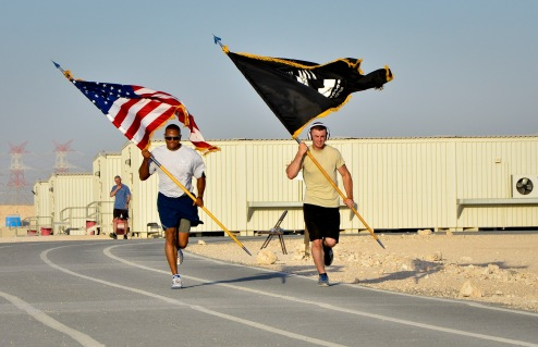 Service members deployed to the 379th Air Expeditionary Wing participate in the 24-hour prisoners of war and missing in action vigil run at the 379th AEW in Southwest Asia, Sept. 21, 2013. The run began Sept. 20 and culminated with a closing ceremony and traditional flag folding by the base honor guard in reverence to those still missing. (U.S. Air Force photo/Staff Sgt. Benjamin W. Stratton)