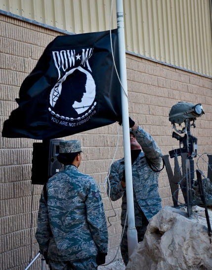 Staff Sgts. Vanessa Dominguez and Ernest McGachey secure the prisoners of war and missing in action flag during a remembrance ceremony at the 379th Air Expeditionary Wing in Southwest Asia, Sept. 21, 2013. In the United States, National POW/MIA Recognition Day is observed on the third Friday in September and honors those who were prisoners of war and those who are still missing in action. Dominguez is assigned to the 379th Expeditionary Force Support Squadron, deployed from March Air Reserve Base, Calif., and hails from El Centro, Calif. McGachey is assigned to the 71st Expeditionary Air Control Squadron and deployed from Spangdahlem Air Base, Germany. (U.S. Air Force photo/Staff Sgt. Benjamin W. Stratton)