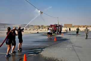 Service members participate in a fire muster event at the 379th Air Expeditionary Wing in Southwest Asia, Sept. 28, 2013. Teams had to get the bucket past their opponent's cone by blasting the bucket with water during this event. More than 80 service members in 20 teams pitted their might in a firefighting flavored challenge wrestling everything from hoses and tires to water buckets and fire trucks. (U.S. Air Force photo/Staff Sgt. Benjamin W. Stratton)