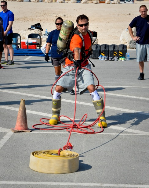 1st Lt. Ben Hosbein pulls a hose reel during a relay race as part of a fire muster event at the 379th Air Expeditionary Wing in Southwest Asia, Sept. 28, 2013. Hosbein is deployed from Robins Air Force Base, Ga., and a St. Joseph, Mich., native. (U.S. Air Force photo/Staff Sgt. Benjamin W. Stratton)