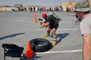 Tech. Sgt. Derek Woodard smacks a tire with a sledgehammer during a relay race as part of a fire muster event at the 379th Air Expeditionary Wing in Southwest Asia, Sept. 28, 2013. Woodard is deployed from Robins Air Force Base, Ga., and a Forsyth, Ga., native. (U.S. Air Force photo/Staff Sgt. Benjamin W. Stratton)