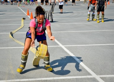 1st Lt. Sharon Kroening rolls out a hose reel during a relay race as part of a fire muster event at the 379th Air Expeditionary Wing in Southwest Asia, Sept. 28, 2013. Kroening is deployed from Robins Air Force Base, Ga., and hails from Osan Air Base, South Korea. (U.S. Air Force photo/Staff Sgt. Benjamin W. Stratton)