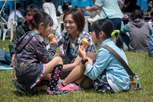 A Japanese mother and her two daughters enjoy ice cream cones during the 28th Annual American Day showcasing the region's bilateral partnership among U.S. military and Japanese residents in Misawa City, Japan, June 5, 2016. The more than 80,000 annual attendees interact with volunteers from private base organizations scattered around at various American-based food booths sharing a taste of home. Americans and Japanese also participate in activities such as a family fun run, an American-themed parade, sports tournaments, street performances and a haunted house. (U.S. Air Force photo by Staff Sgt. Benjamin W. Stratton)